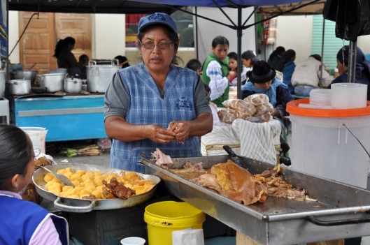 The meat the lady has in her hands in the hornado (roasted pork). The small yellow balls are mashed potatoes that are the Llapingachos.