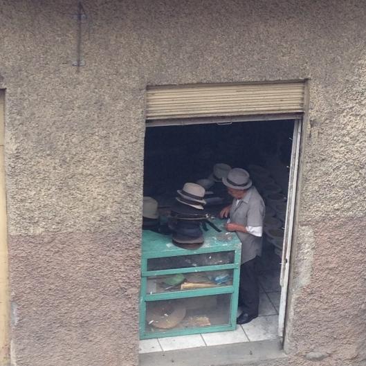 A man repairs Panama hats in his tiny shop.